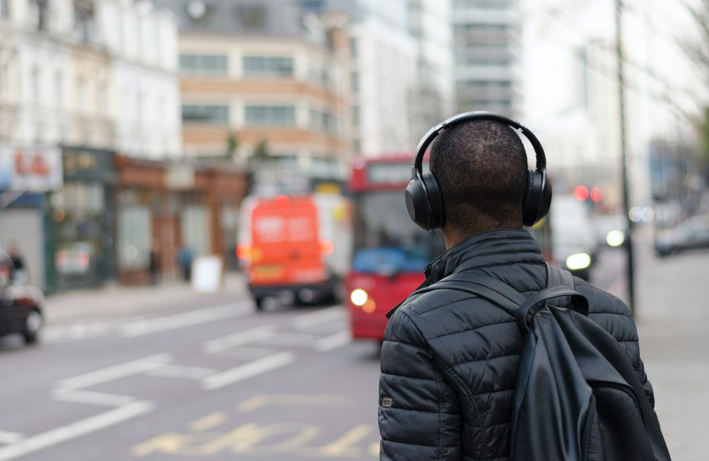 Man wearing headphones waiting for a bus