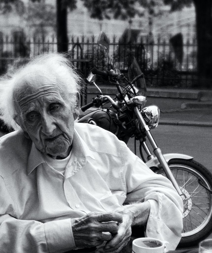 Old man sitting sadly near a motorcycle